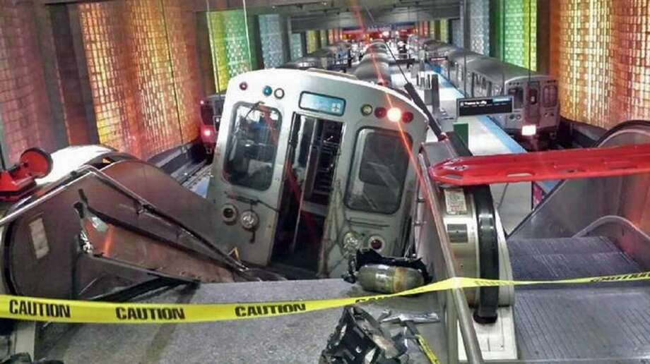 "A Chicago Transit Authority train car rests on an escalator at the O'Hare Airport station after it derailed early Monday, March 24, 2014, in Chicago. More than 30 people were injured after the train ""climbed over the last stop, jumped up on the sidewalk and then went up the stairs and escalator,"" according to Chicago Fire Commissioner Jose Santiago. Photo: Kenneth Webster"