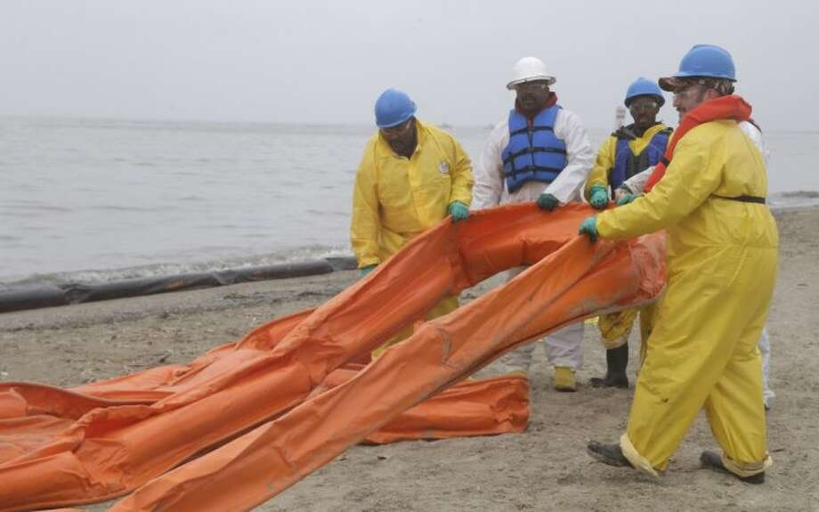 An oil spill clean up crew drags a boom along East Beach in Galveston, Texas, Monday, March 24, 2014. Thousands of gallons of tar-like oil spilled into the major U.S. shipping channel after a barge ran into a ship Saturday. Photo: Pat Sullivan