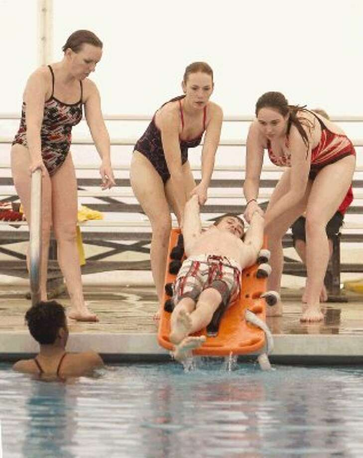 Ryan Reed gets lifted out of the water on a board by Deborah Strong and Hannah McNease as instructor Genn Bedore looks on during an American Red Cross lifeguard training session at the Conroe Aquatic Center Saturday. Photo: Jason Fochtman