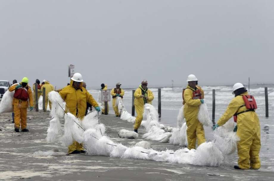A crew spreads a viscous snare along East Beach to trap oil Monday, March 24, 2014, in Galveston, Texas. Thousands of gallons of tar-like oil spilled into the major U.S. shipping channel after a barge ran into a ship Saturday. Photo: Pat Sullivan