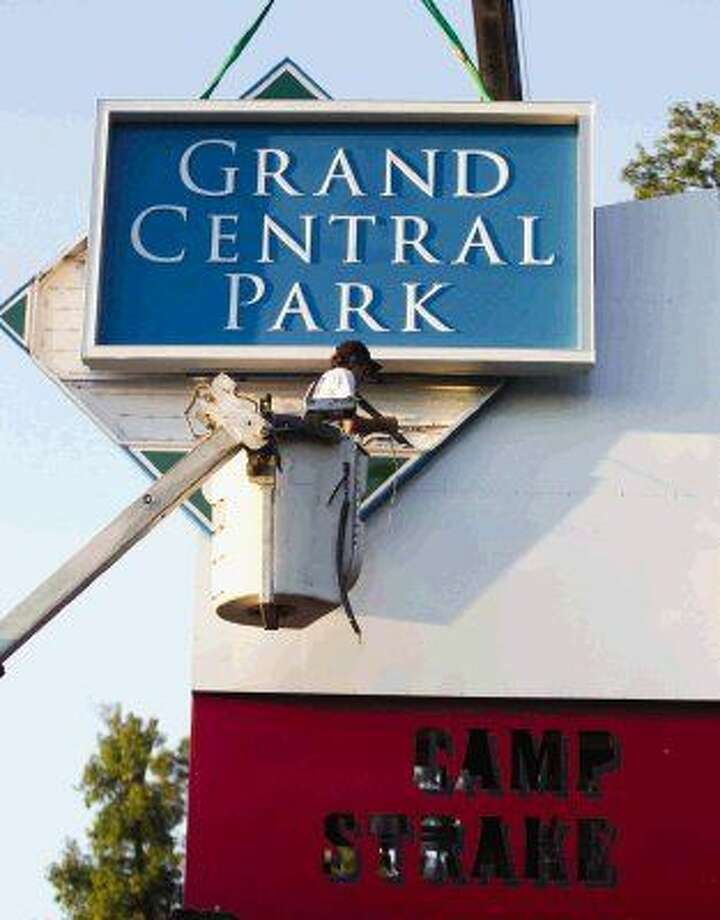 Workers install a sign for Grand Central Park, the site of the former Camp Strake property, last September. Photo: Jason Fochtman