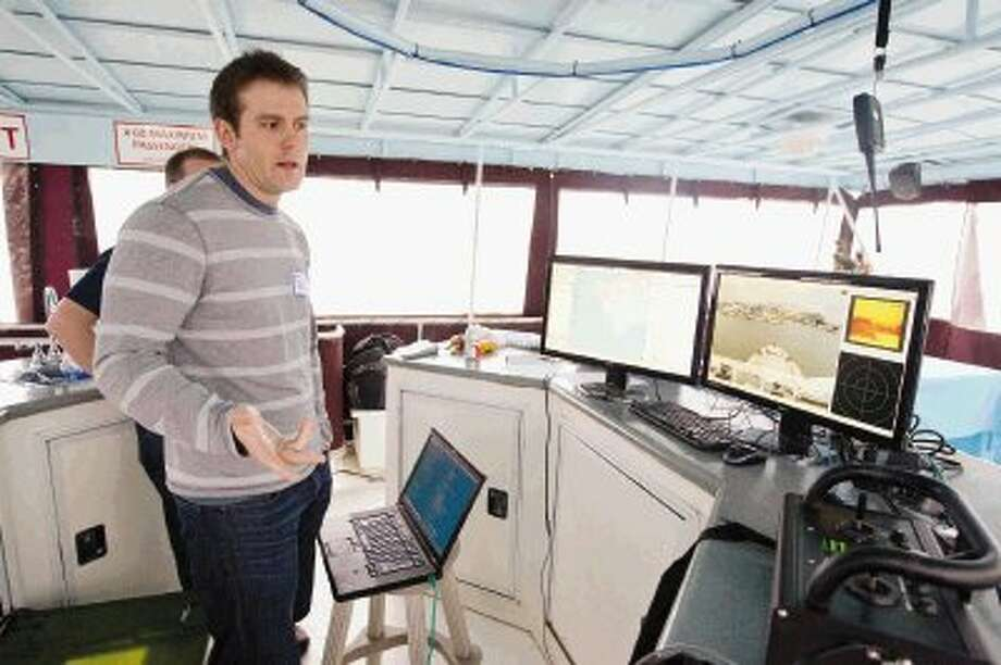 Programmers from C&C Technologies: Survey Services talk about the company's new autonomous surface vessel on Lake Conroe Thursday. The vessel can be accessed from anywhere in the world via satellites and boasts night vision capabilities as well as four moveable cameras. Data points and locations can also be added from any computer. Photo: Jason Fochtman / Conroe Courier / HCN