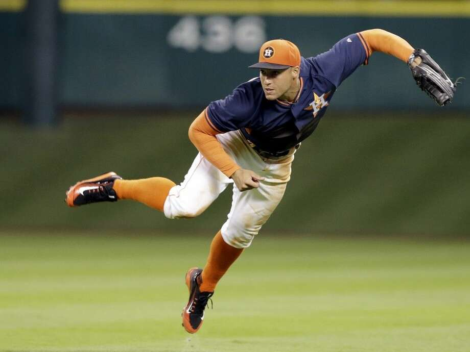 Houston Astros right fielder George Springer is airborne after throwing to home in the fifth inning Friday in Houston. Photo: Pat Sullivan