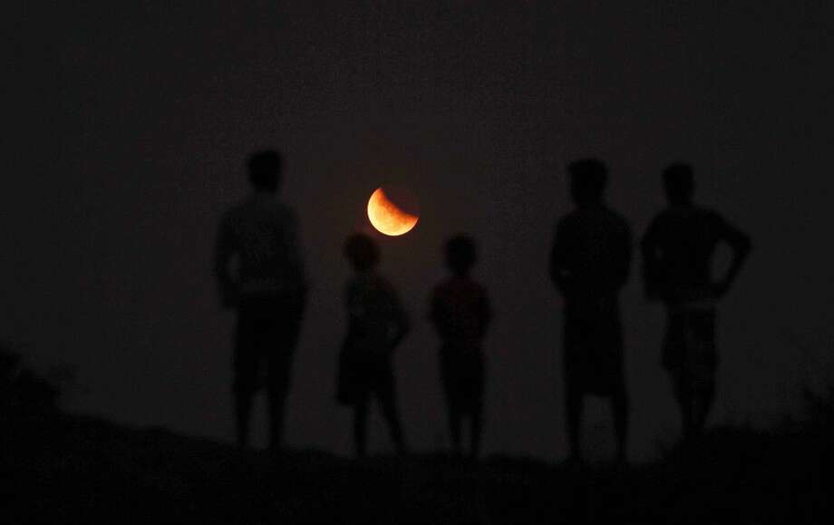 Indians watch a lunar eclipse from the banks of River Kuakhai on the outskirts of Bhubaneswar on Saturday.