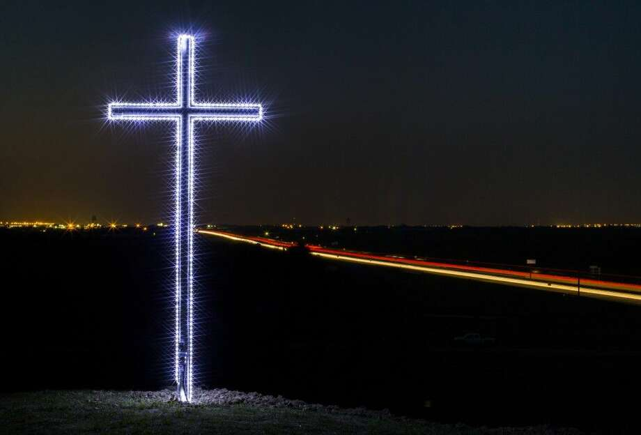 In this April 2, photo, vehicle lights on Interstate 45 can be seen from an illuminated cross that stands at the north end of the Old Brickyard Golf Course in Ferris, Texas. The cross, which was erected in 1930 was recently refurbished. Photo: Ashley Landis