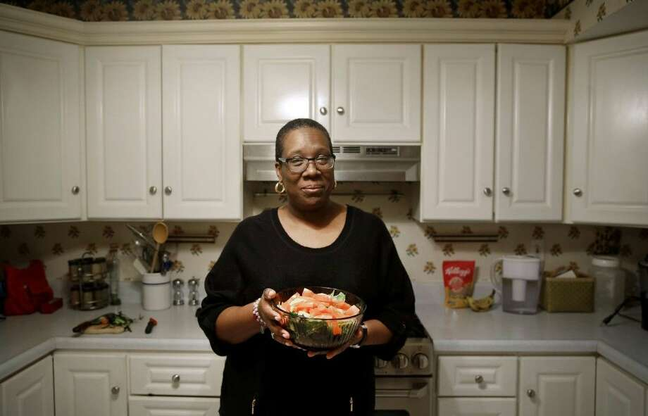 In this April 3, photo, Michele Rouse holds a salad that she made in her kitchen in Edgewood, Md. Rouse says she has lost 7 pounds since she started on Weight Watchers a month ago and has already seen a drop in her elevated blood pressure. Photo: Patrick Semansky