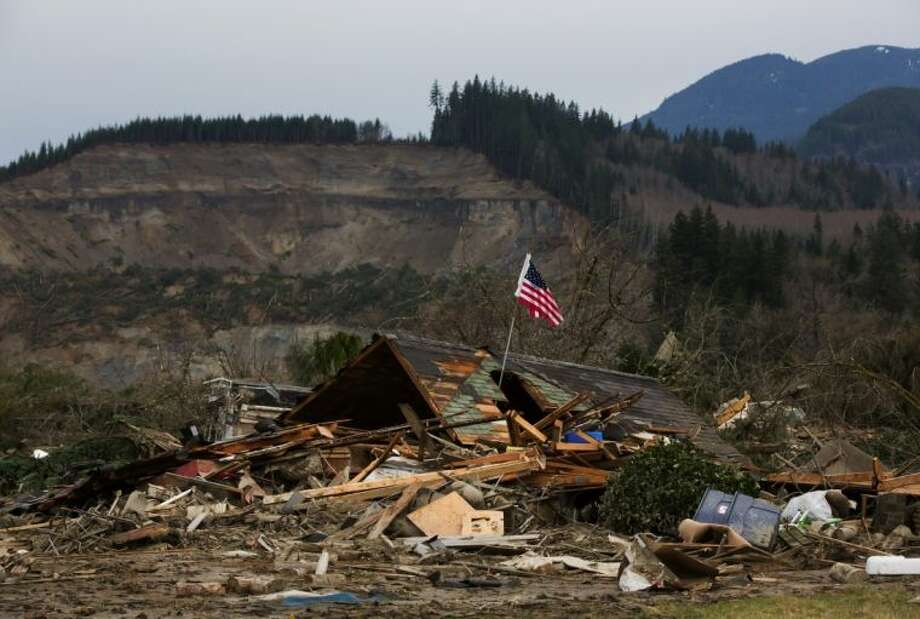 A damaged home sits in the debris field caused by Saturday's massive mudslide above the North Fork of the Stillaguamish River onto Highway 530, as recovery efforts continue near Oso, Wash., on Tuesday, March 25, 2014. A scientist working for the government had warned 15 years ago about the potential for a catastrophic landslide in the community where the collapse of a rain-soaked hillside over the weekend killed at least 14 people and left scores missing. Photo: Marcus Yam