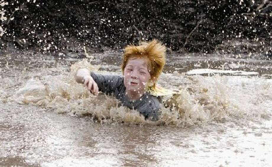 Hyden Jilek swims through the mud pit near the finish line during the inaugural Montgomery Madness 5K Mud Run in May 2013. The event helped raise money to benefit the Montgomery High School Class of 2014 Project Graduation. Go to HCNPics.com to view and purchase this photo, and others like it. Photo: Staff Photo By Jason Fochtman / Conroe Courier