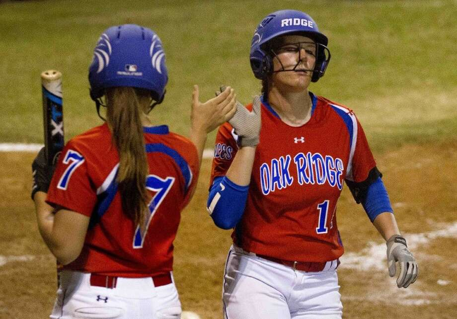 Oak Ridge's Haley Nillen, right, gets a high-five from Kylie Hunt after scoring a run in the third innning during a District 16-6A softball game at Conroe High School Tuesday. Go to HCNpics.com to purchase this photos, and other like it. Photo: Jason Fochtman