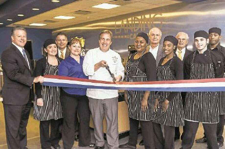 John Brazie (center), executive chef at The Woodlands Resort & Conference Center, cuts the ribbon to officially open The Landing Café, a new eatery at One Hughes Landing at Hughes Landing on Lake Woodlands. Joining him (left to right) are: Greg Parsons, general manager and vice president of Hospitality for The Woodlands Resort & Conference Center; Bianca Aroche, staff member at The Landing Café; Eric Rabel, senior project manager, Development, for TWDC; Wendy Hamrick, manager of The Landing Café; Alex Sutton (back row), co-president of TWDC; Peter Doyle, executive vice president, Development, for The Howard Hughes Corporation and front row, Darlene Williams, Mariya Linton, Tim Burton and Chris Baldwin, staff members at The Landing Café. / Ted Washington