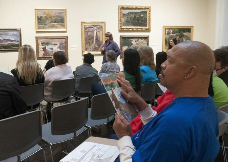 """In this March 15 photo, Bobby Jackson, who is sight impaired, feels a textured copy of a Joaquin Sorolla y Bastida painting as artist John Bramblitt, who is blind, leads a workshop on the Spanish artist's painting, """"The Blind Man of Toledo,"""" at Southern Methodist University's Meadows Museum in Dallas. The Meadows is on the cutting edge of efforts not only to reach out to the visually impaired but also to offer multisensory experiences that appeal to a wide range of audiences through touch, sound and taste."""
