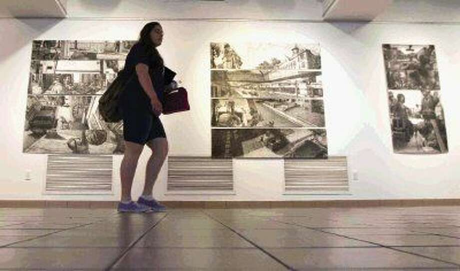 "A student on Wednesday walks through ""Time and Place,"" an exhibit by Christopher Troutman, at Lone Star College-Montgomery. Photo: Jason Fochtman"