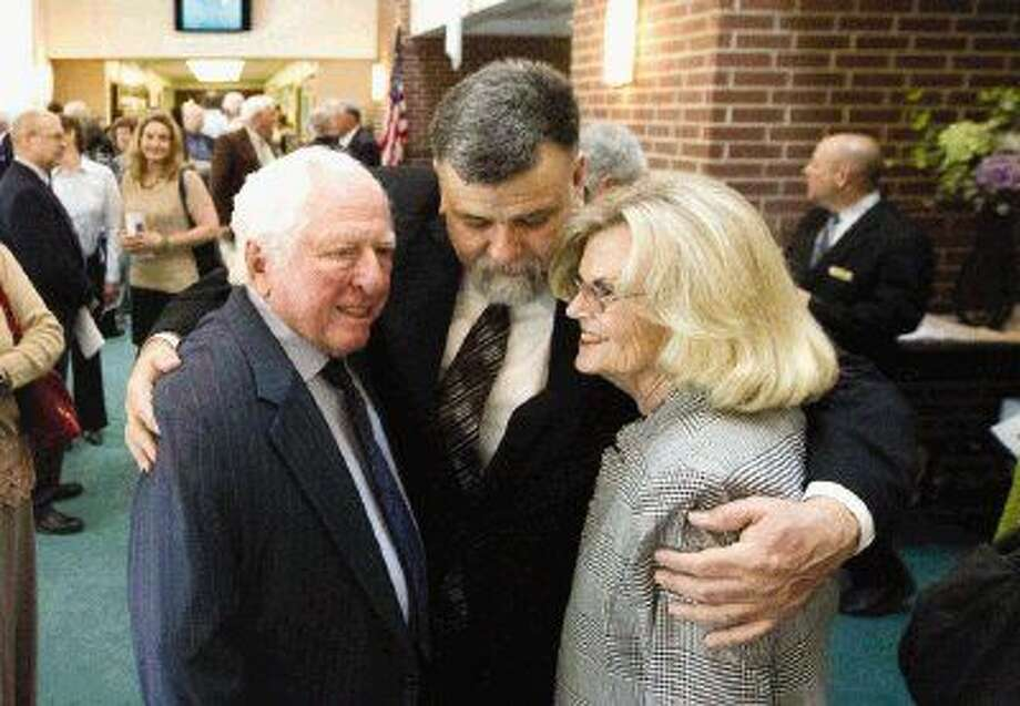 Ryan Alworth, son of retired Judge Lee G. Alworth, center, hugs Henry Brooks, left, and Frankie Alexander before the start of his father's funeral service Wednesday at First United Methodist Church. Photo: Jason Fochtman