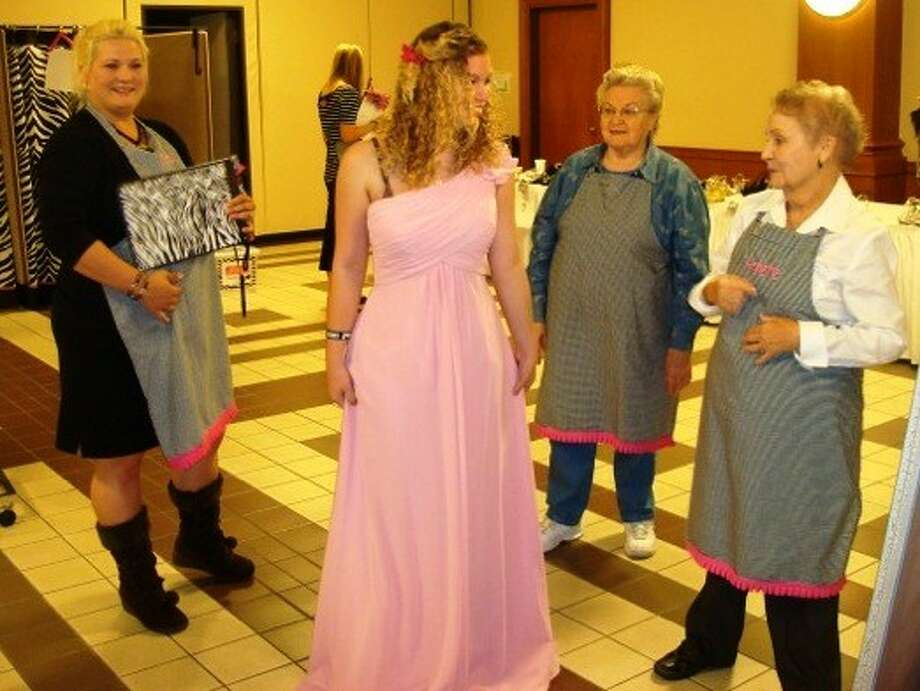"First Baptist Church Priceless Gowns ministry volunteers, above and below, assist with dressing high school juniors and seniors for the prom. Students can shop for a ""priceless"" gown Friday and Saturday for this year's prom."