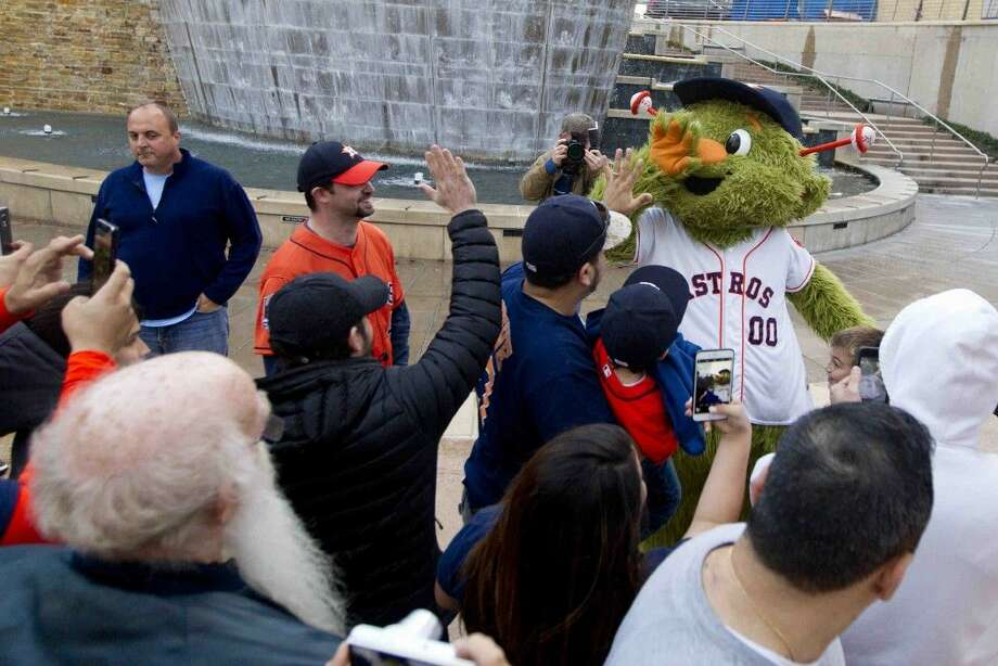 Houston Astros mascot Orbit gives fans high-fives during an Astros Caravan stop at The Woodlands Waterway Thursday.