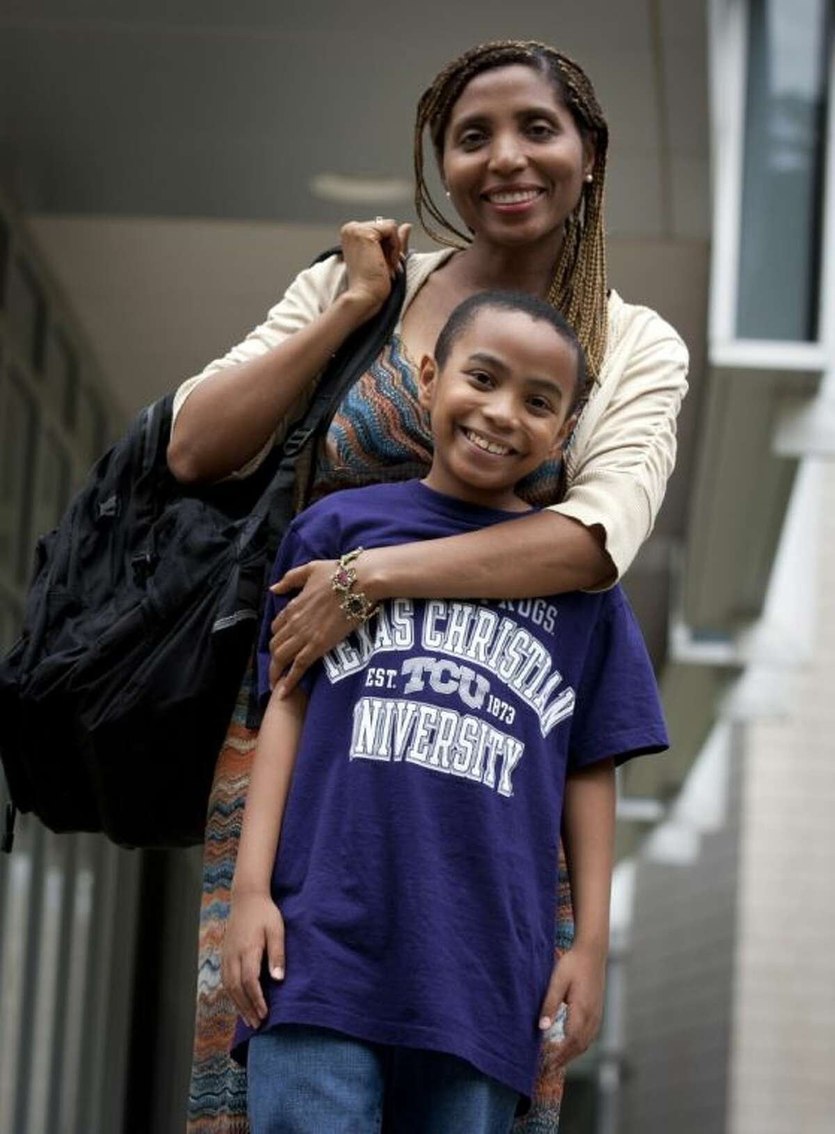 In this Tuesday photo, Carson Huey-You, 11, who is studying quantum physics at TCU, poses for a photo with his mother, Claretta Huey-You, in Fort Worth. He became TCU's youngest student ever when classes started last week. The physics major says he plans to be a quantum physicist.