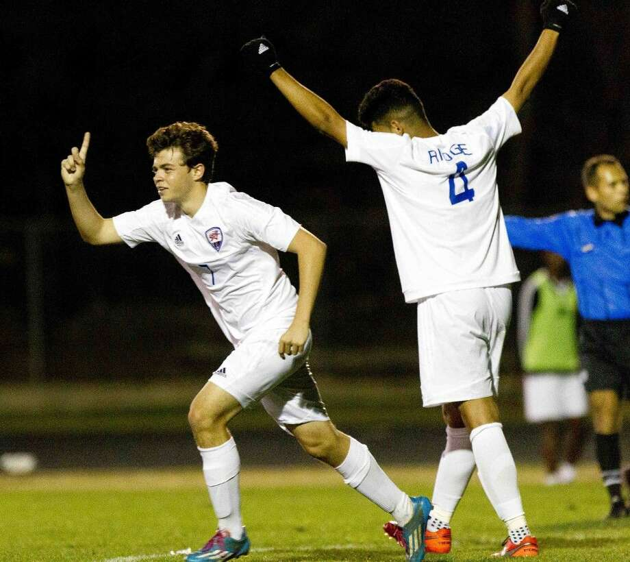 Oak Ridge's Brian Strippe, left, celebrates along with Christian Treto after scoring the game tying goal off a free kick during the second period of a District 16-6A boys soccer game Wednesday. G Photo: Jason Fochtman