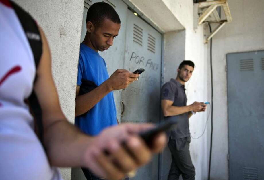 "Students gather behind a business looking for a Internet signal for their smart phones in Havana, Cuba, Tuesday, April 1, 2014. The U.S. Agency for International Development masterminded the creation of a ""Cuban Twitter,"" a communications network designed to undermine the communist government in Cuba, built with secret shell companies and financed through foreign banks, The Associated Press has learned. The project, which lasted more than two years and drew tens of thousands of subscribers, sought to evade Cuba's stranglehold on the Internet with a primitive social media platform. Its users were neither aware it was created by a U.S. agency with ties to the State Department, nor that American contractors were gathering personal data about them. In 2012, the text messaging service vanished as mysteriously as it appeared. Photo: Ramon Espinosa"