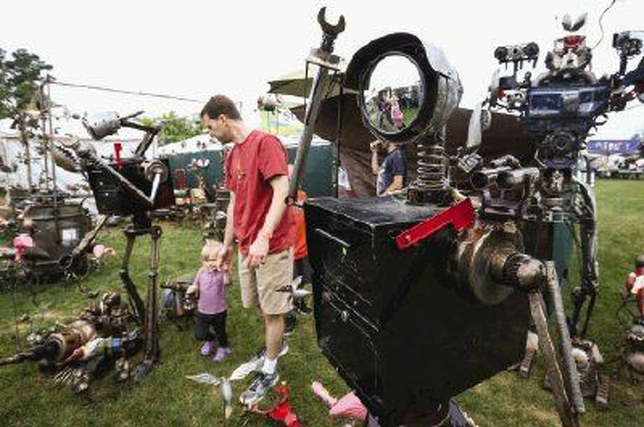 Woodlands resident Matt Griswald, right, walks with his daughter Mia through a collection of metalworks by Fred Conlon of Salt Lake City, Utah, during The Woodlands Waterway Arts Festival on Saturday, April 11, 2015, on The Woodlands Waterway near Town Green Park.