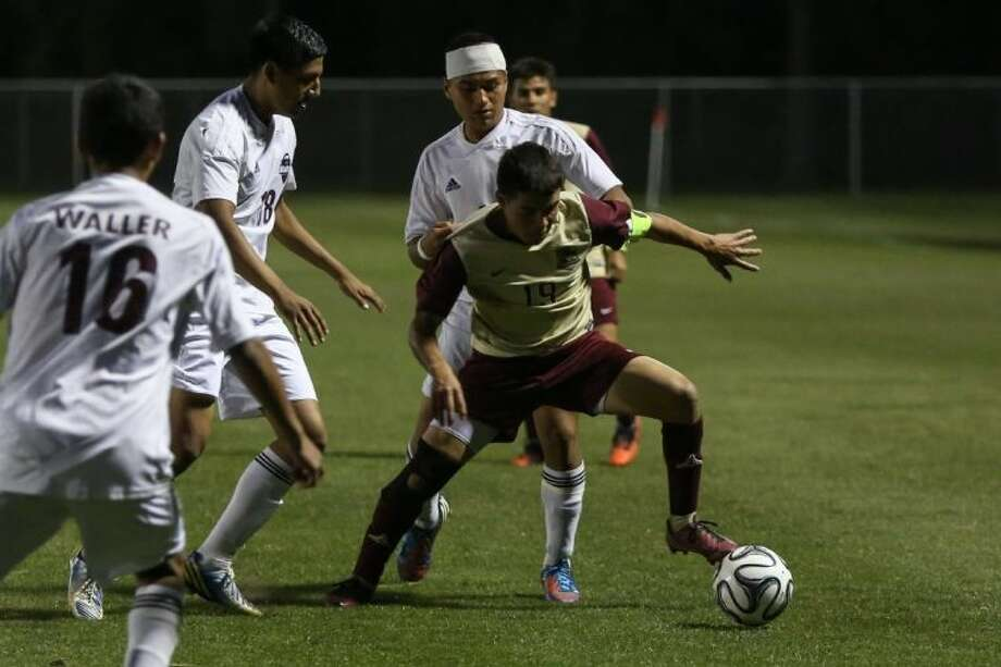 Magnolia West's Miguel Miranda (19) struggles for possession of the ball against several Waller defenders during the high school soccer game. Waller defeated the Mustangs 2-1. Photo: Michael Minasi