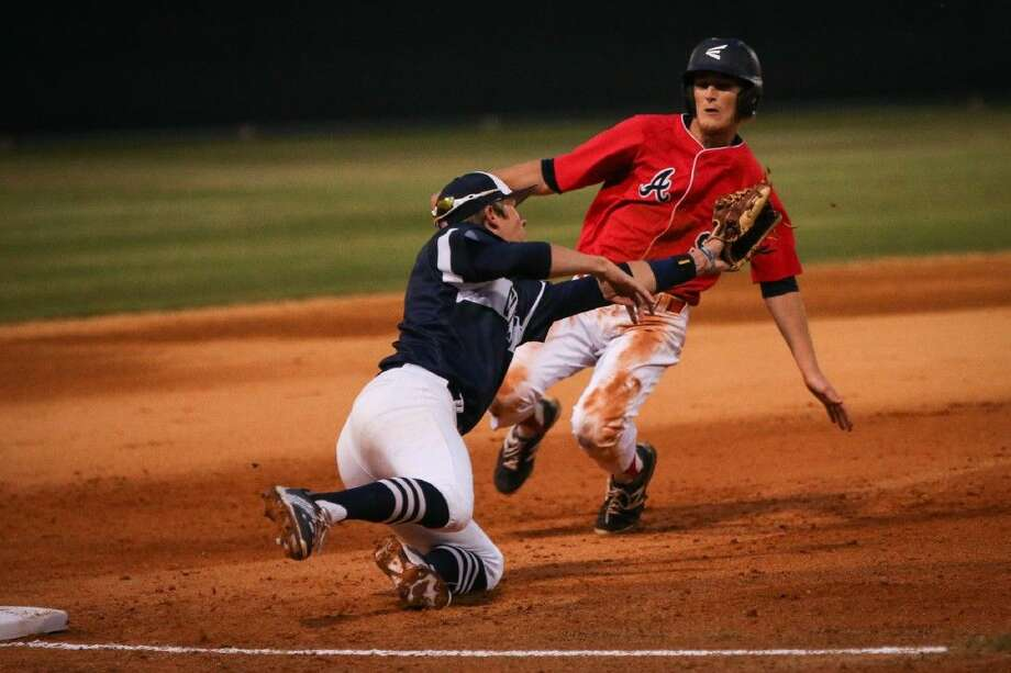 College Park's Chandler Morris tries to tag Atascocita's Stephen Hunter on Friday at College Park High School. Photo: Michael Minasi