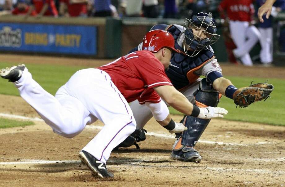 Houston Astros catcher Jason Castro, right, reaches out to put the tag on Texas Rangers' Jake Smolinski, left, during the fifth inning of a baseball game Saturday, April 11, 2015, in Arlington, Texas. Castro but dropped the ball on the play to allow a run. Photo: John F. Rhodes