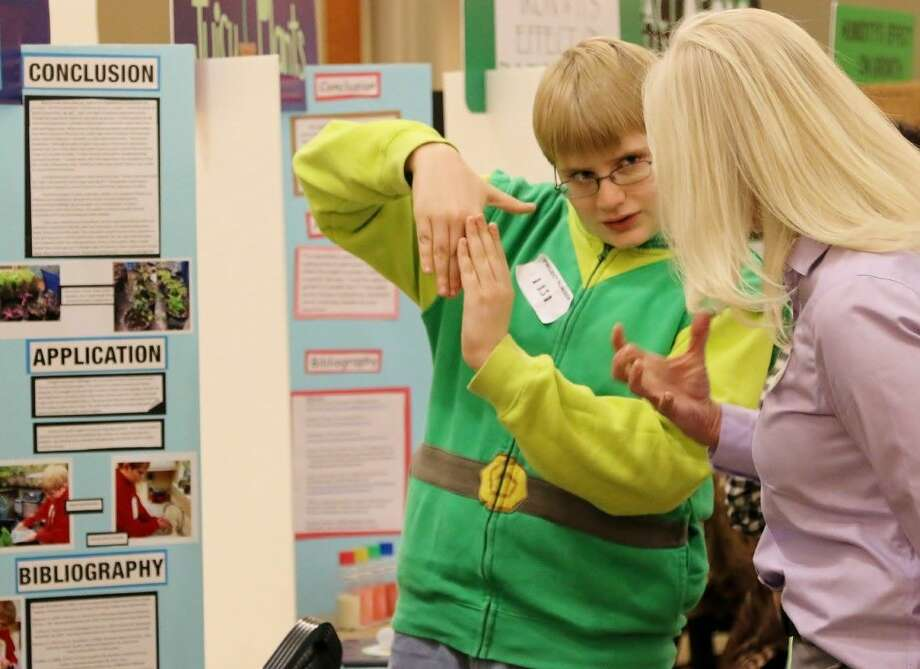 Wynter Japp, a Conroe ISD student, describes his project during the SCI://TECH Junior High Science Fair.
