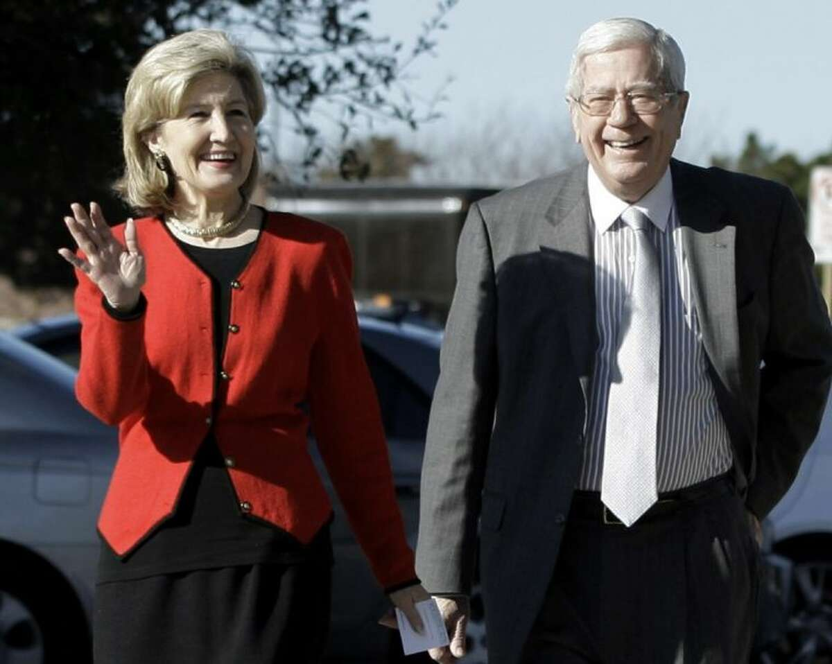 In this Feb. 16, 2010 file photo attorney Ray Hutchison, right, a former legislator, gubernatorial candidate and the husband of former U.S. Sen. Kay Bailey Hutchison, left, walks to a rally for his wife in Dallas.