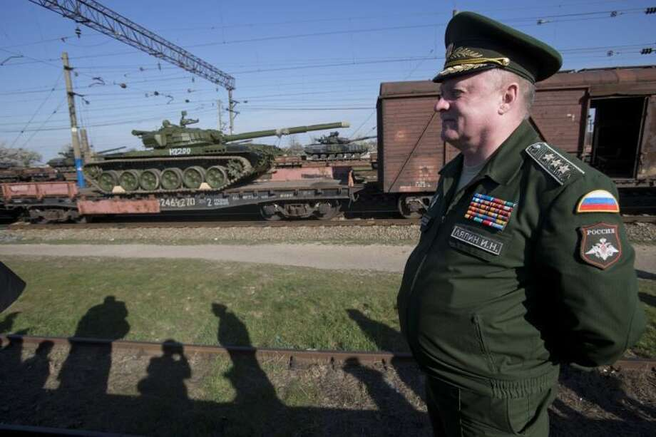 Russian head of Transport Department of the Ministry of Defense Colonel General Igor Lyapin smiles as Russian tanks T-72B, close left, arrive and Ukrainian tanks T-62, center back, are transported to the Ukraine at the Ostryakovo railway station not far from Simferopol, Crimea, Monday, March 31, 2014. Photo: Pavel Golovkin