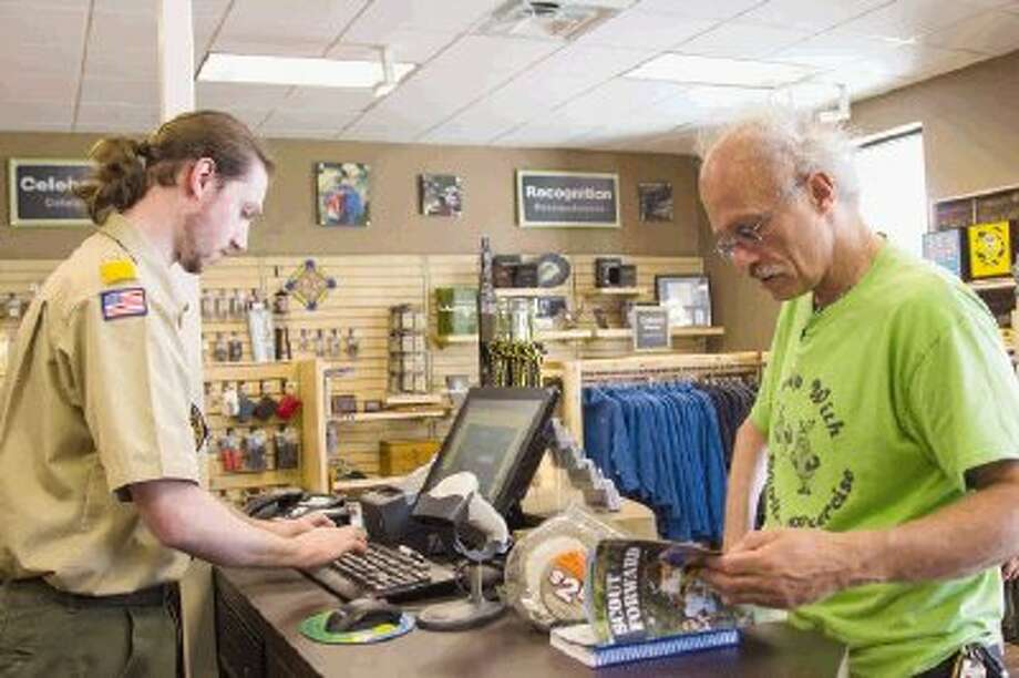 John Peak, a store clerk, rings up books for Greg Zillmer during the opening of Strake Scout Shop in Conroe on Monday. The store moved from Camp Strake to West Dallas Street. Photo: Staff Photo By Ana Ramirez / The Conroe Courier/ The Woodland
