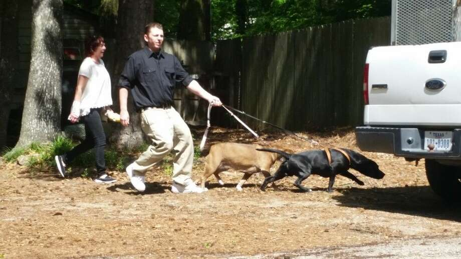Nathan White and his mother Shirley White lead their dogs to a waiting Montgomery County Animal Control deputy Monday. The dogs were seized after being deemed dangerous last year for killing numerous cats and chasing pedestrians in the Walden community.