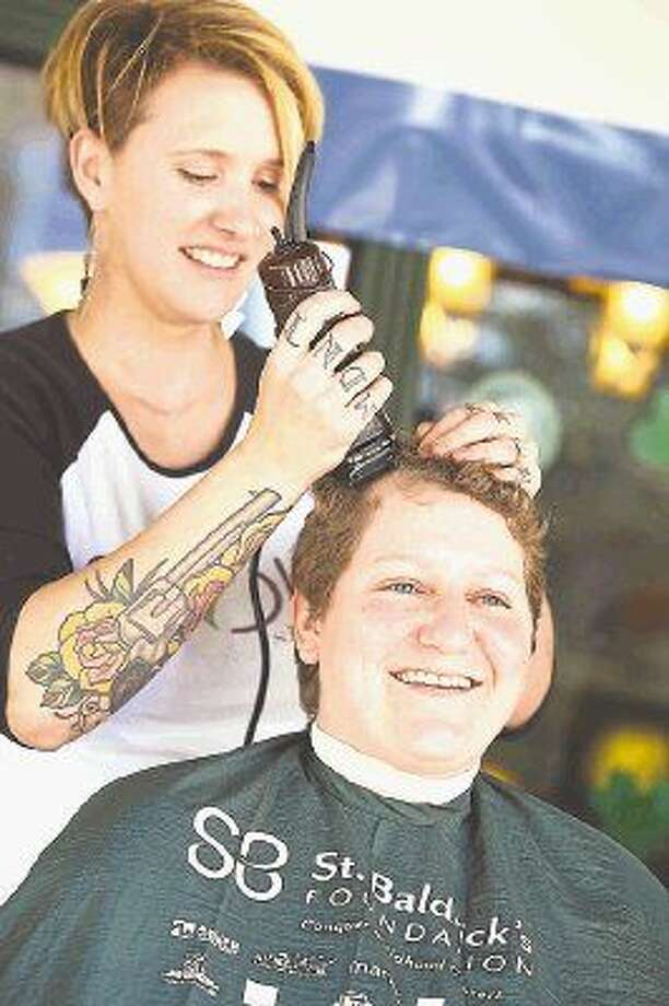 Stylist Jenny Jordan shaves the head of 12-year cancer survivor Margaret Glover of Spring at the St. Baldrick's Day event March 15, 2015 at The Gooses Acre Irish Bistro and Pub. This year's event will be from 3 p.m. Sunday at The Gooses Acre. Photo: Michael Minasi