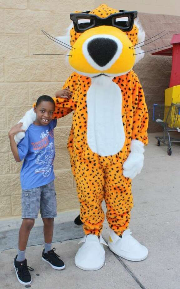 Nine-year old Damarion Swift was happy to meet Chester Cheetah at the Walmart grand reopening in Cleveland on Saturday, Sept. 14, which was also Swift's birthday. Photo: RACHEL HALL