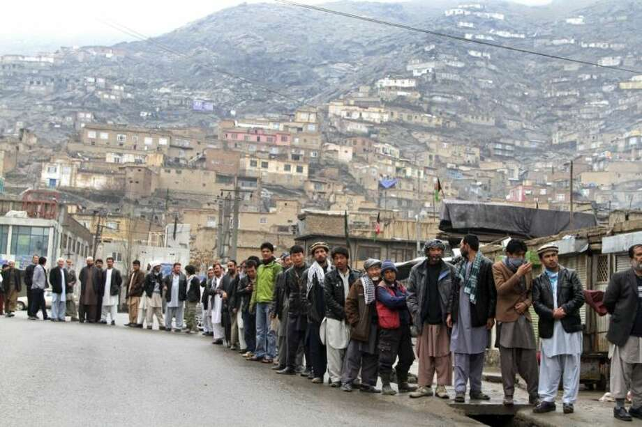 Afghan men line up outside a polling station to cast their ballots in Kabul, Afghanistan, Saturday.