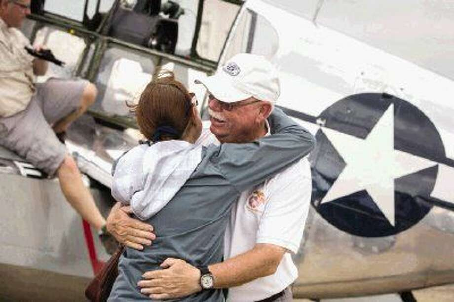Montgomery resident Bruce Longley hugs his wife, Barbara, after successfully flying a P-51C Mustang, a WWII era fighter plane, during the Wings of Freedom Tour on Monday at Conroe-North Houston Regional Airport.