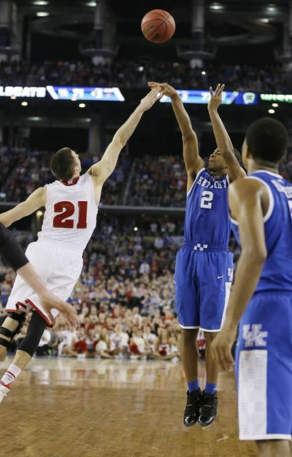 Kentucky guard Aaron Harrison, right, shoots the winning 3-pointer over Wisconsin's Josh Gasser on Saturday night. Kentucky will face UConn in the national title game. Photo: Charlie Neibergall