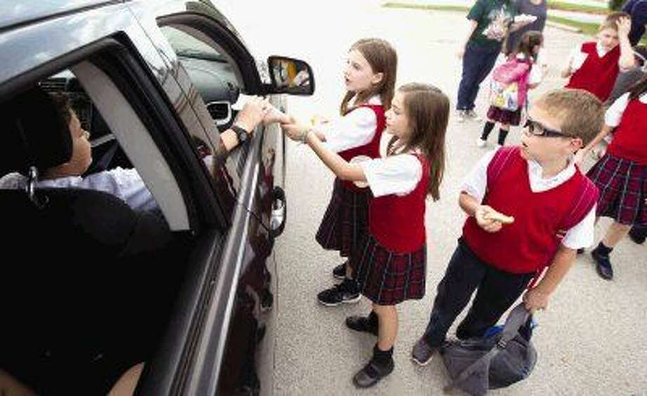 Students from Sacred Heart Catholic School hand out cookies and lemonade after classes Wednesday. Students accepted donations as part of The Great Lemonade War. Every $50 funds one hour of childhood cancer research. Their goal is to raise $2,000.