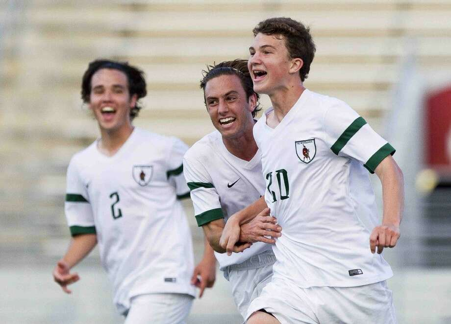 The Woodlands Jacob Moore, center, celebrates a goal by Ryder Sousa during the second period of a District 16-6A boys soccer game Friday. Photo: Jason Fochtman