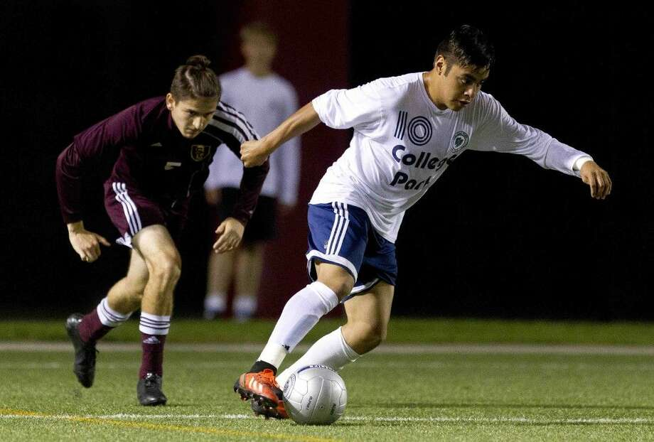 College Park's Rodrigo Perez dribbles the ball past Summer Creek's Alejandro Martinez during the first half of a District 16-6A boys soccer game Friday. Go to HCNpics.com to purchase this photo, and others like it. Photo: Jason Fochtman