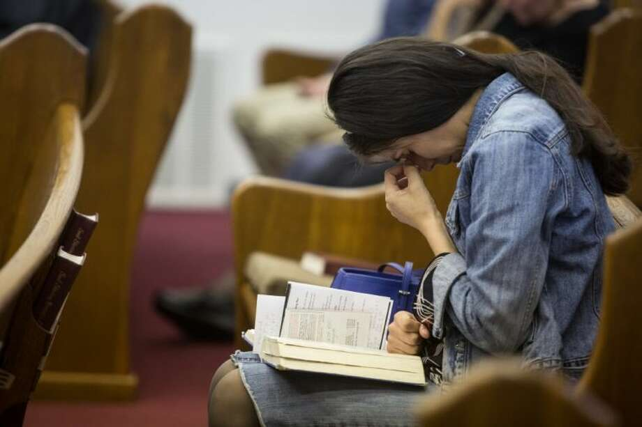 Kathy Abad, a military wife, prays for the victims and families affected by the Fort Hood shooting during a memorial service at the Tabernacle Baptist Church on Sunday, April 6, 2014, in Killeen, Texas.
