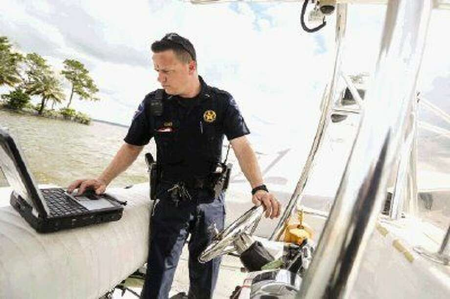 Lieutenant Tim Cade, with Montgomery County Precinct 1 Constable's Office, looks up the information for a boat that was found drifting on Lake Conroe after water levels surged 2 feet above the maximum capacity Friday. Photo: Michael Minasi