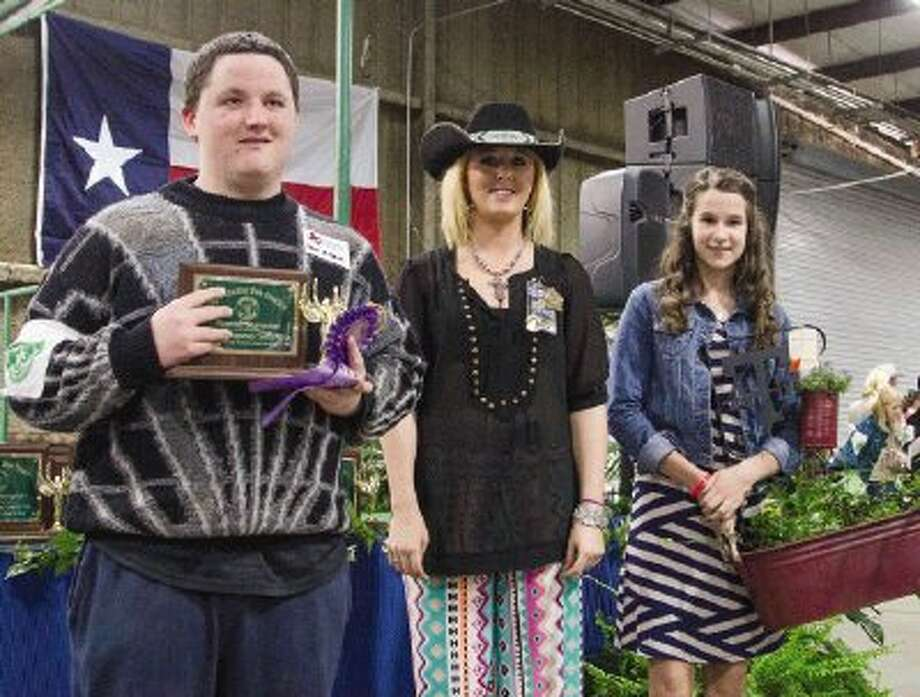 Sean Mitchell, of Willis High School, receives a trophy for placing Reserve for his Horticulture exhibit at the 2014 Montgomery County Fair Special Education Show during the Montgomery County Fair and Rodeo in Conroe Monday. / The Conroe Courier/ The Woodland