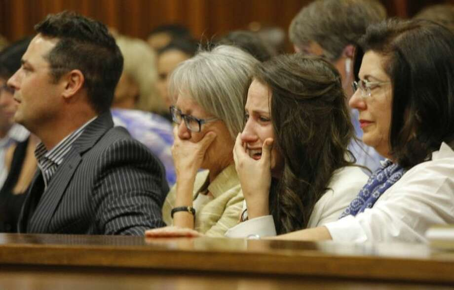 Sister of Oscar Pistorius, Aimee Pistorius, second from right, cries as she listens as her brother testifies in court in Pretoria, South Africa, Tuesday, April 8, 2014. Pistorius is charged with the murder of his girlfriend Reeva Steenkamp, on Valentines Day 2013. Photo: Kim Ludbrook