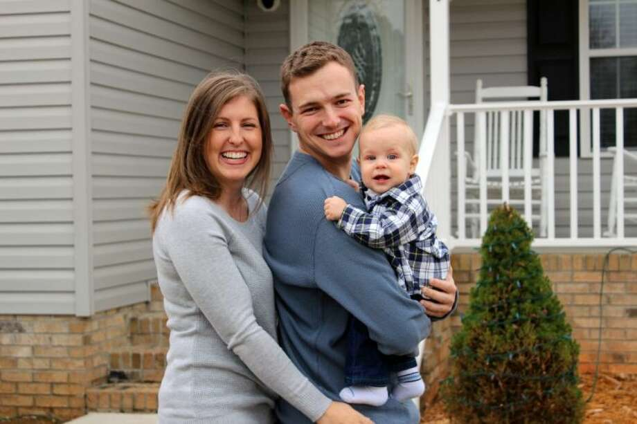 This Dec. 7, 2013 photo shows, from left, Tricia Williamson, her husband Mike Williamson, and their one-year-old son Adam at their home in Liberty, N.C. Tricia Williamson, 30, in Liberty, N.C., quit her job as an editor and producer at a TV station after crunching the numbers and realizing her salary after the birth of her son a year ago would go primarily to her commuting and child care expenses.
