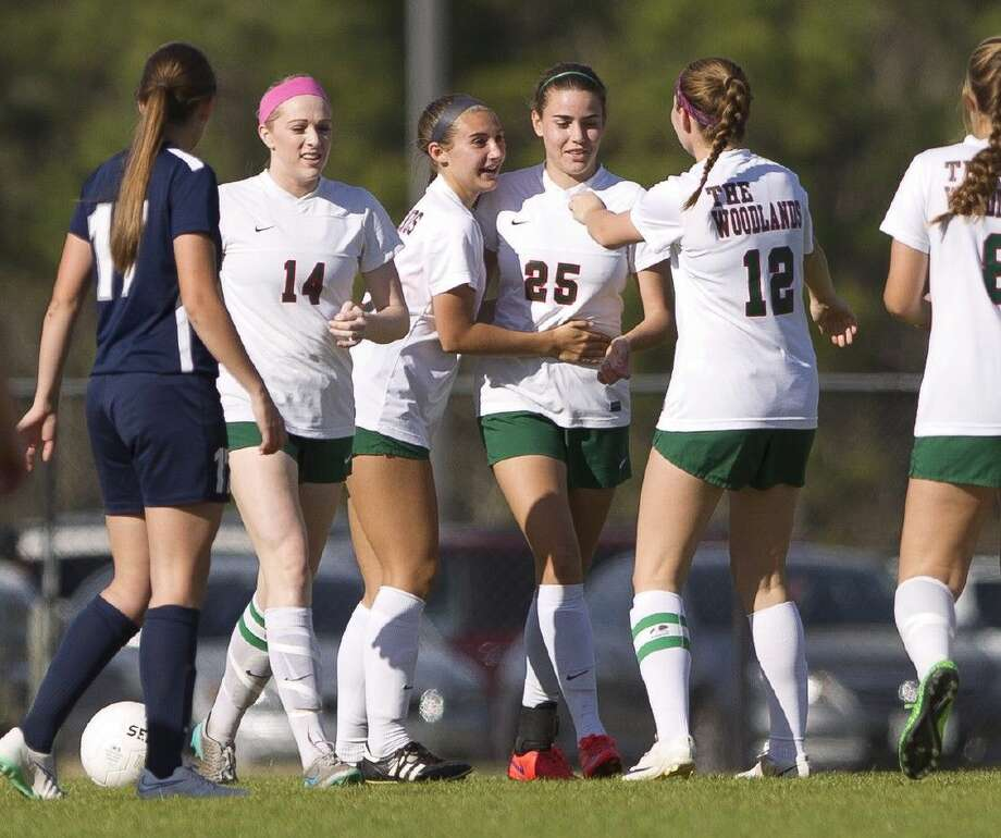 The Woodlands players celebrate with Katie Krotee (25) after her second period goal during a District 16-6A girls soccer game Saturday. Photo: Jason Fochtman