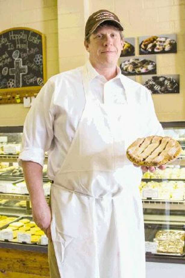 Tim Schenk, the owner of Montgomery Bakehouse on North Frazier Street in Conroe, holds one of the many pies and other assorted pastries baked fresh at his family bakery each day - often from family recipes. Photo: Staff Photo By Ana Ramirez / The Conroe Courier