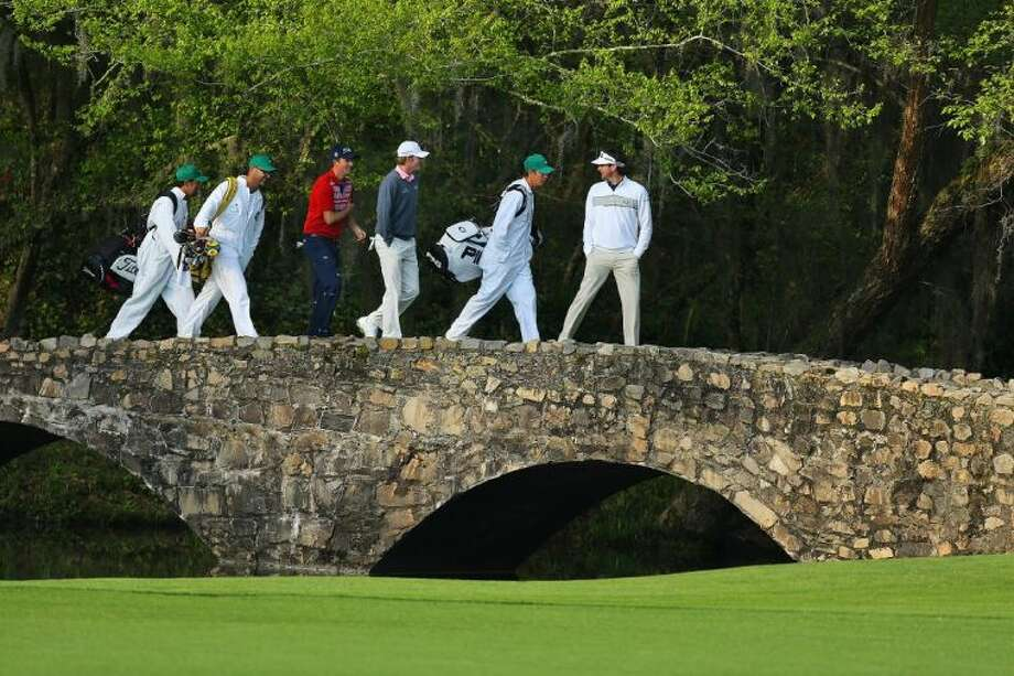 From left with their caddies, Webb Simpson, Brandt Snedeker and Bubba Watson cross the Byron Nelson Bridge after teeing off on the 13th hole during a practice round for the Masters on Wednesday in Augusta, Ga. Photo: Curtis Compton