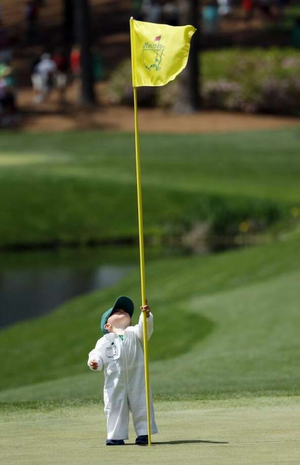 Scott Stallings's son Finn looks at the flag on the fourth green during the Par 3 competition at the Masters on Wednesday in Augusta, Ga. Photo: Matt Slocum