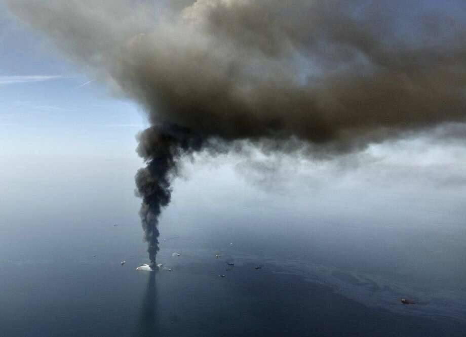 FILE - In this April 21, 2010 file photo by Gerald Herbert, the Deepwater Horizon oil rig burns in the Gulf of Mexico. Rig fires happen with some regularity, but when word came that the rig was listing badly after an explosion the night before, New Orleans-based Gerald Herbert raced to a small airport and grabbed the first helicopter pilot he could find. Together with a photographer from the Times-Picayune newspaper, the three headed out in a four-seat helicopter with only enough fuel to get to the site and shoot for a few minutes. Photo: Gerald Herbert