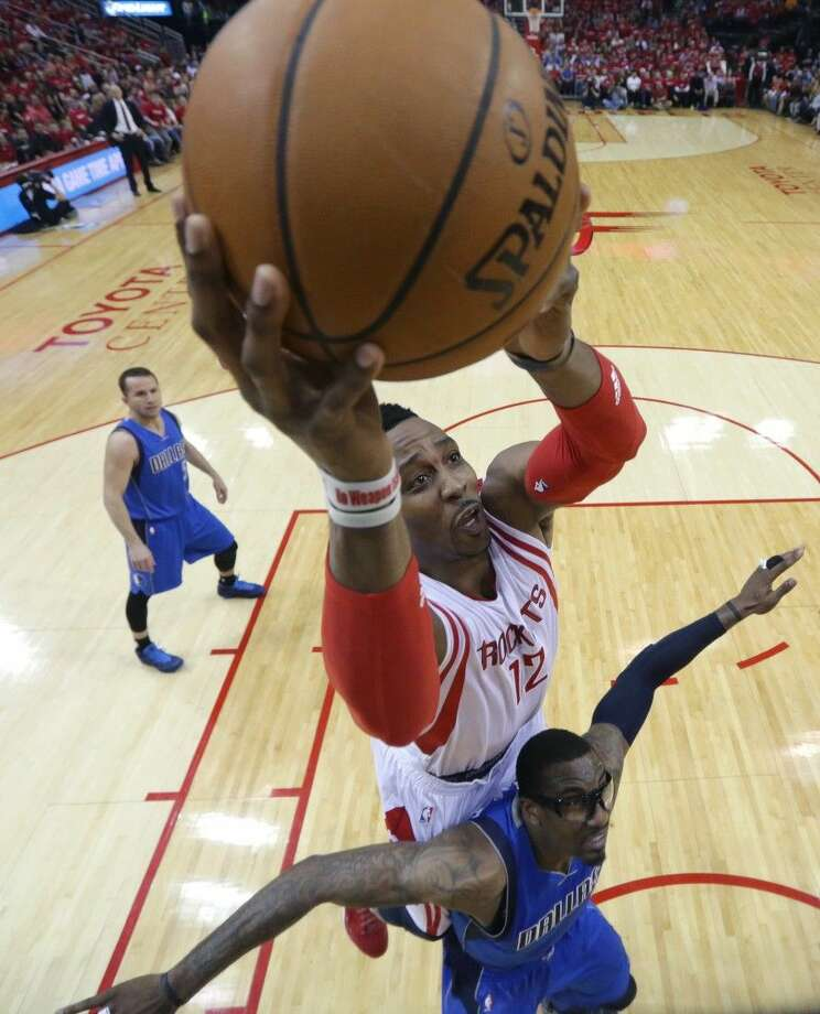 The Rockets' Dwight Howard (12) scores over the Mavericks' Amar'e Stoudemire. Photo: David J. Phillip